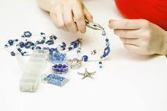 Femme faisant le necklase à partir des perles en plastique colorées sur le fond clair photo libre de droits