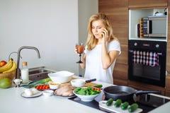Femme faisant le repas sain et lisant le message au téléphone dans la cuisine domestique Image stock