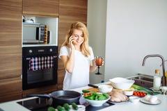 Femme faisant le repas sain et lisant le message au téléphone dans la cuisine domestique Photos libres de droits