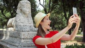 Femme faisant le selfie avec la statue de sphinx au téléphone portable dans le mouvement lent en villa Borghese le jour ensoleill clips vidéos
