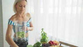 Femme faisant le smoothie végétal vert avec le mélangeur Mode de vie sain de consommation banque de vidéos