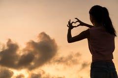 Femme faisant le symbole de coeur avec ses mains au coucher du soleil Photo libre de droits