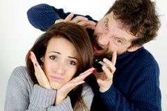 Femme faisant le visage drôle tandis que le mari hurle à elle Image stock