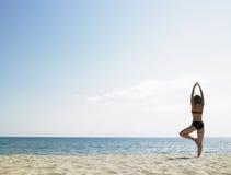 Femme faisant le yoga à la plage photographie stock libre de droits