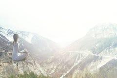 Femme faisant le yoga au-dessus d'une montagne Photographie stock