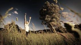 Femme faisant le yoga au milieu d'un champ de haute herbe - évaluation de style de sépia - mouvement lent banque de vidéos