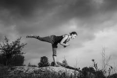 Femme faisant le yoga contre le coucher de soleil Image stock
