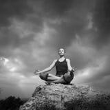 Femme faisant le yoga contre le coucher de soleil Photo stock