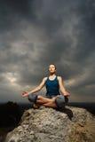 Femme faisant le yoga contre le coucher de soleil Images stock