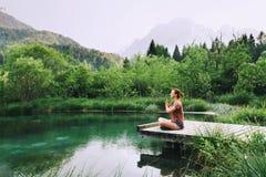 Femme faisant le yoga et méditant en position de lotus sur la nature images stock