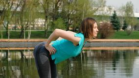 Femme faisant le yoga ou le sport par l'étang, dehors banque de vidéos