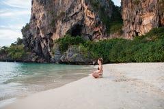 Femme faisant le yoga sur la plage photographie stock libre de droits