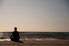 Femme faisant le yoga sur la plage. Image libre de droits