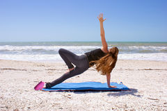 Femme faisant le yoga sur la plage dans la planche latérale Photo stock
