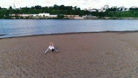 Femme faisant le yoga sur la plage par la rivière dans la ville Belle vue banque de vidéos