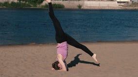 Femme faisant le yoga sur la plage par la rivière dans la ville Belle vue handstand Ficelle dans le ciel vitesse possible élevée  clips vidéos