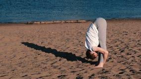 Femme faisant le yoga sur la plage par la rivière dans la ville Belle vue dans la pose de Padangustasana banque de vidéos