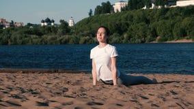 Femme faisant le yoga sur la plage par la rivière dans la ville Belle vue dans la pose de shvanasana d'Urdhva Mukha clips vidéos