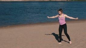 Femme faisant le yoga sur la plage par la rivière dans la ville Belle vue Roue de gymnastique banque de vidéos