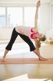 Femme faisant le yoga sur le couvre-tapis dans le studio Images libres de droits