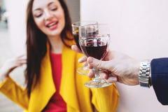 Femme faisant tinter le verre de vin rouge avec l'homme dehors Photographie stock libre de droits