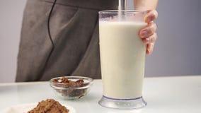 Femme faisant un cocktail fruité laiteux dans un mélangeur, préparation de smoothies clips vidéos