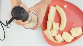 Femme faisant un cocktail fruité laiteux dans un mélangeur, préparation de smoothies 4K banque de vidéos