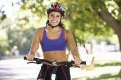 Femme faisant un cycle par le parc photos libres de droits