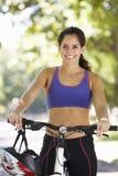 Femme faisant un cycle par le parc image stock