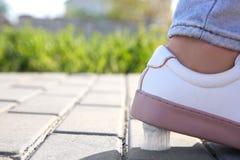 Femme faisant un pas dans le chewing-gum sur le trottoir Photographie stock
