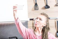 Femme faisant un selfie dans sa cuisine Photographie stock