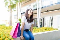 Femme faisant une pause des achats tout en se reposant en dehors du mail photo stock