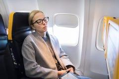 Femme faisant une sieste sur le siège tout en voyageant en avion photos libres de droits