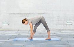 Femme faisant à yoga la pose intense de bout droit sur le tapis Photographie stock libre de droits
