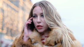 Femme fascinante heureuse attirante dans le manteau de fourrure de renard parlant au téléphone, dehors clips vidéos