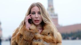 Femme fascinante heureuse attirante dans le manteau de fourrure de renard parlant au téléphone, dehors banque de vidéos