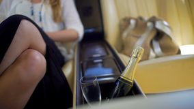 Femme fascinante s'asseyant en voiture chère, bouteille de champagne et plan rapproché en verre Photo stock