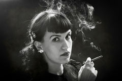 Femme Fatal. Young woman in black holding cigar and smoke Royalty Free Stock Photo