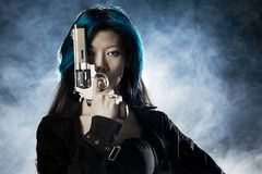 Femme fatale. Asian beauty holding gun with smoke royalty free stock photos