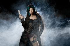 Femme Fatale. Asian beauty holding gun with smoke in background Stock Photography