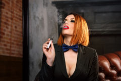 Femme fatale and electronic cigarette. Young attractive girl in a jacket and bow tie smokes electronic cigarette. Femme fatale. Evening makeup smokey eye Stock Photography
