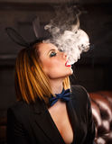 Femme fatale and electronic cigarette. Young attractive girl in a jacket, a butterfly tie and bunny ears smokes an electronic cigarette. Femme fatale. Evening Stock Photos