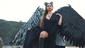 Femme fatale in lange uitstekende zwarte kleding, majestueuze donkere maitresse met grote veervleugels en enge hoornen, bevindt z stock video