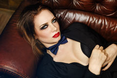 Femme fatale on leather couch Royalty Free Stock Image
