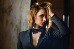 Femme fatale. Passion and desire. Young attractive girl in a jacket and bow tie. Femme fatale. Evening makeup smokey eye. She straightens her hair. Passion and Stock Photo
