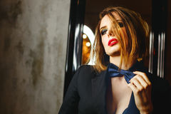 Femme fatale. Passion and desire. Young attractive girl in a jacket and bow tie. Femme fatale. Evening makeup smokey eye. She straightens her tie. Passion and Royalty Free Stock Images