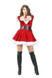Femme fatale szpieg ubierał jako Święty Mikołaj kobieta wskazuje krócicę przy kamerą obraz stock