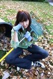 Femme fatigué de ratisser des lames d'automne Photographie stock libre de droits