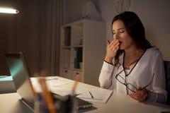 Femme fatiguée avec des papiers baîllant au bureau de nuit image stock