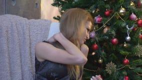 Femme fatiguée ayant la casserole dans le cou sur le fond d'arbre de Noël clips vidéos